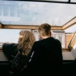To unge mennesker kigger ud af vinduet for at få luft og lys
